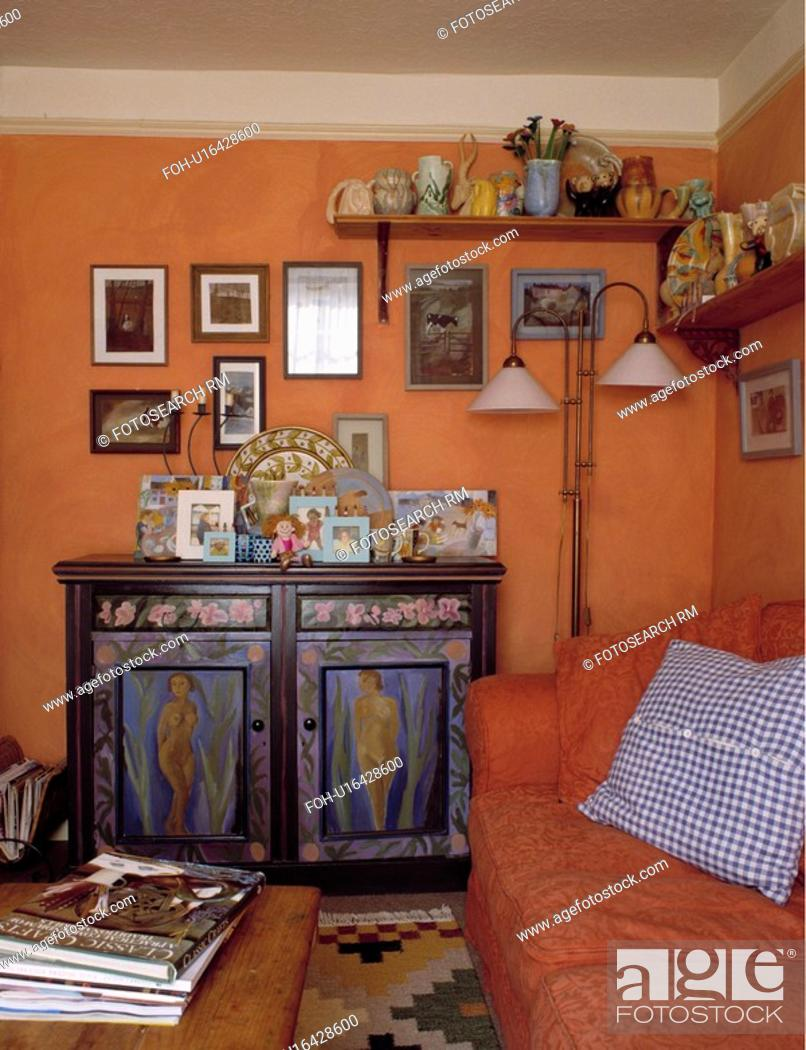 Painted Wooden Cupboard And Orange Sofa In Terracotta Living