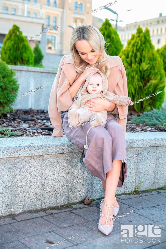 Imagen: Charming happy mother with a small daughter in her arms sitting on the parapet.