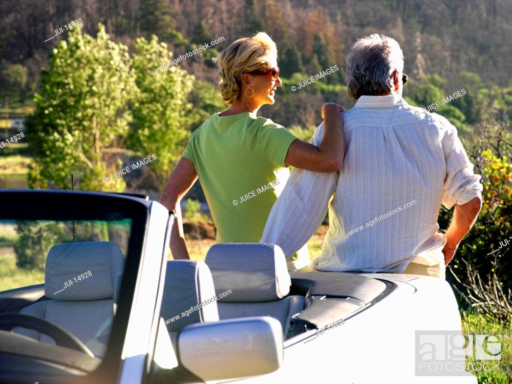 Stock Photo: Couple by car looking at scenery, rear view.