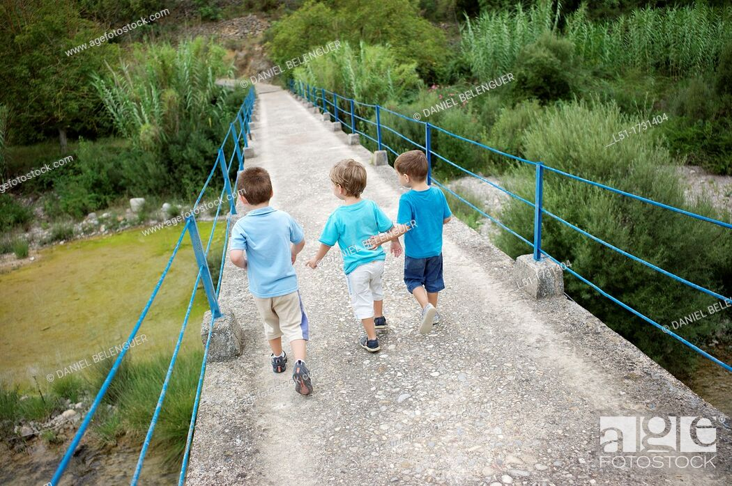 Stock Photo: three boys crossing an old bridge on the country, Ludiente, Castellón, Spain.