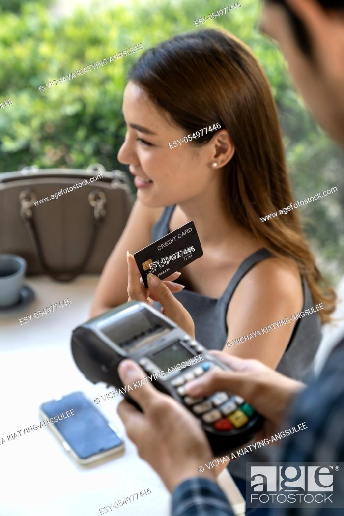 Stock Photo: Asian woman customer hold contactless credit card for making online payment after eating out in new normal social distance restaurant.