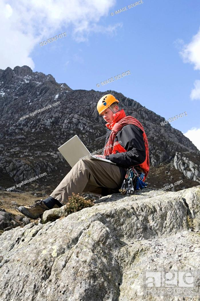Stock Photo: A man using a laptop on a rock.