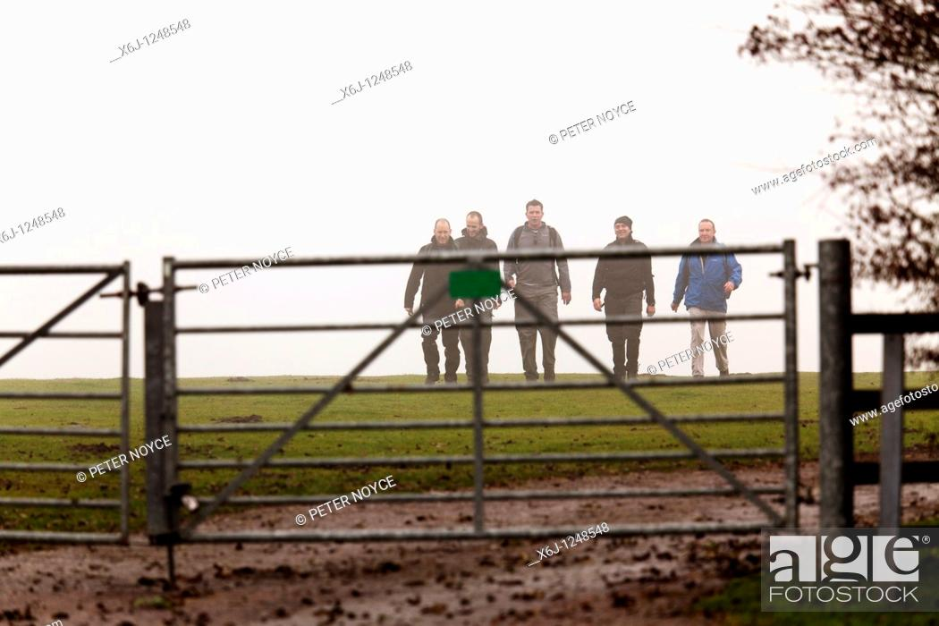 Photo de stock: group of walkers approching metal countryside gate from the mist.