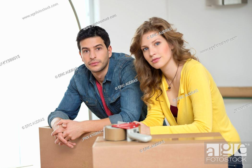 Stock Photo: Couple leaning over cardboard boxes.