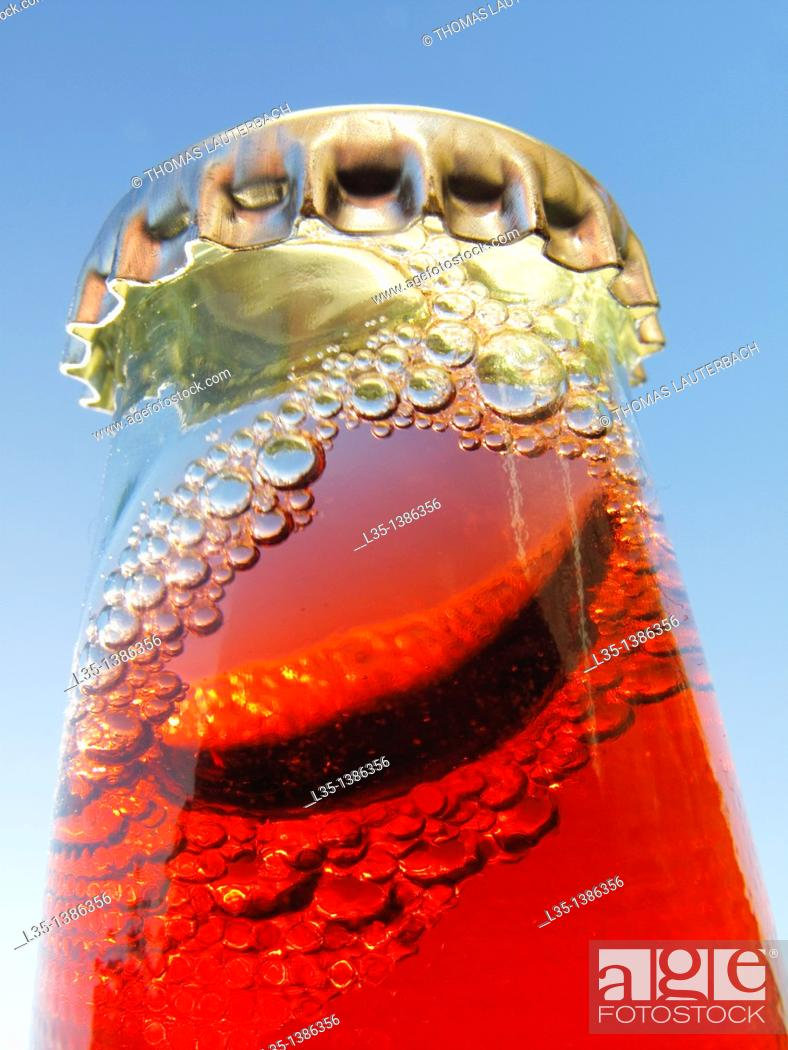 Stock Photo: Shaken bottle neck with crown cap and a red liquid and many bubbles.