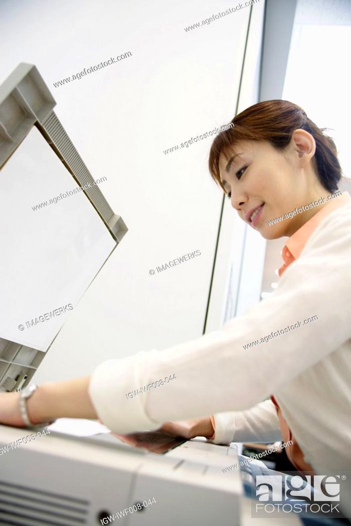 Stock Photo: A woman operating a Xerox machine.