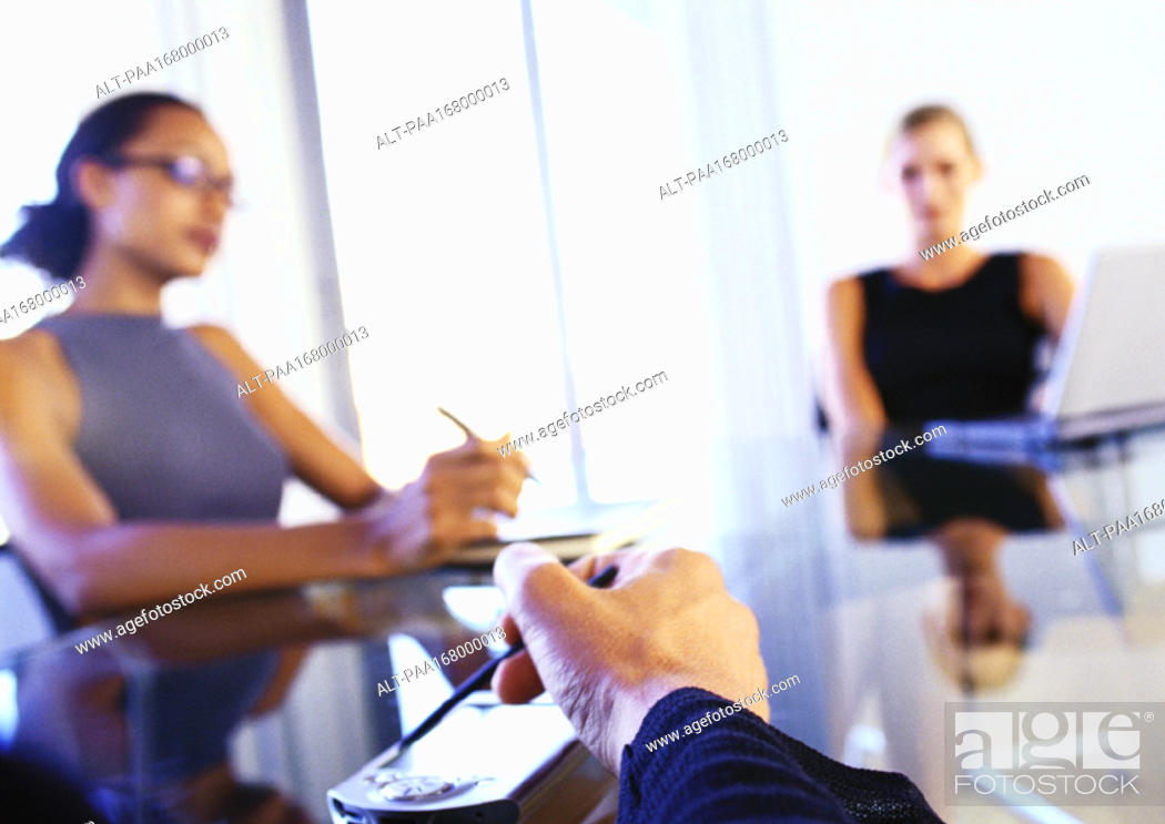 Stock Photo: Businesswomen sitting at desk, man's hand using electronic organizer.