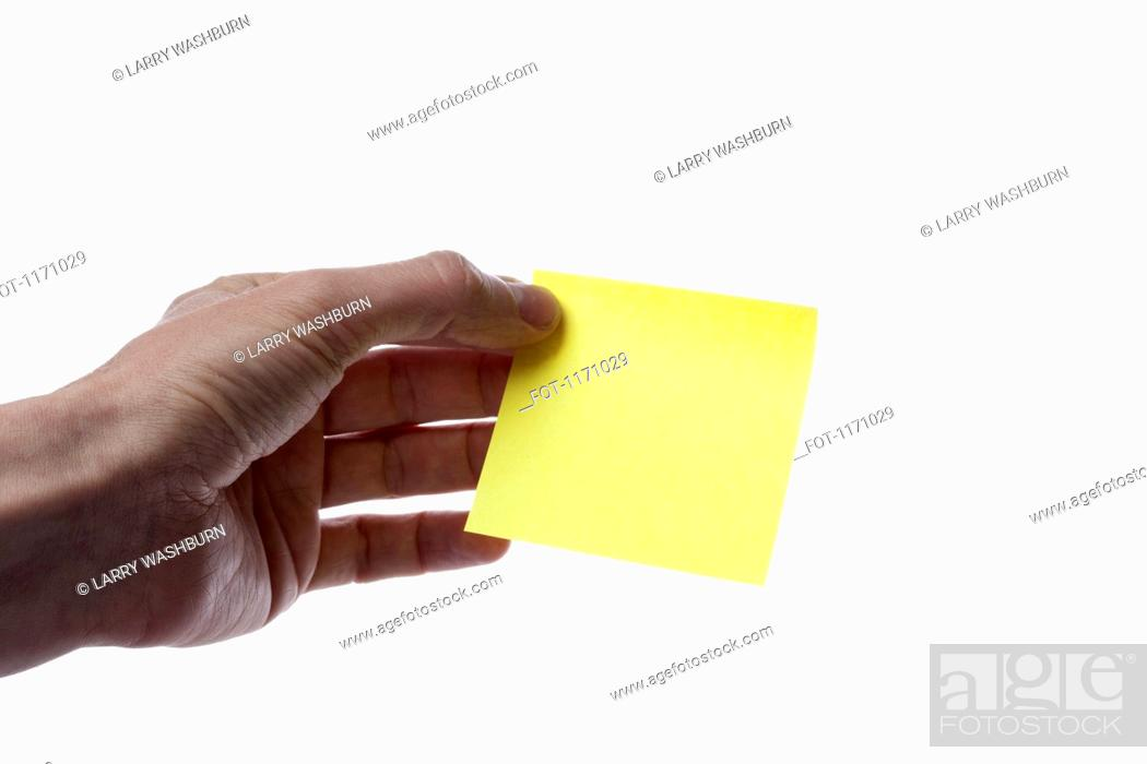 Stock Photo: A man holding a blank yellow adhesive note, close-up of hand.
