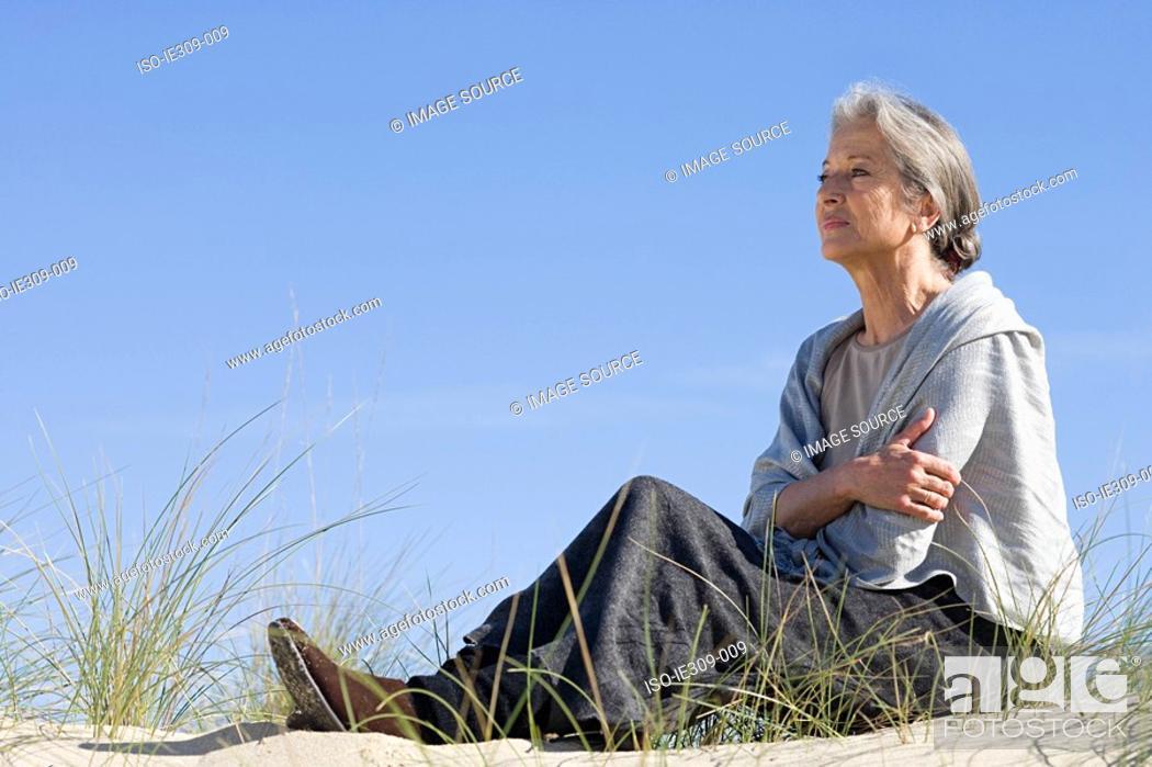 Stock Photo: Senior woman relaxing on a beach.