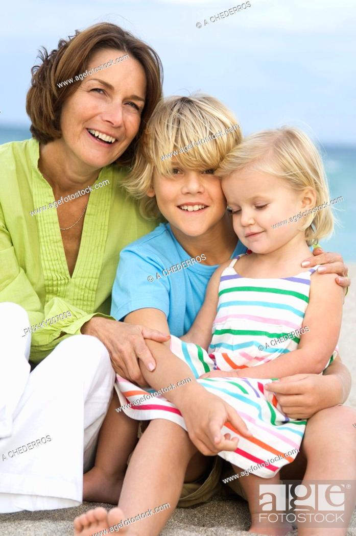 Stock Photo: Woman sitting with her grandchildren on the beach.