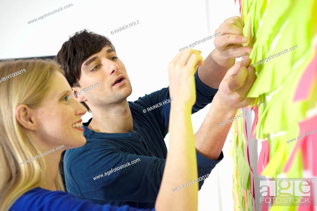 Stock Photo: Germany, Cologne, Man and woman sticking paper note on wall.