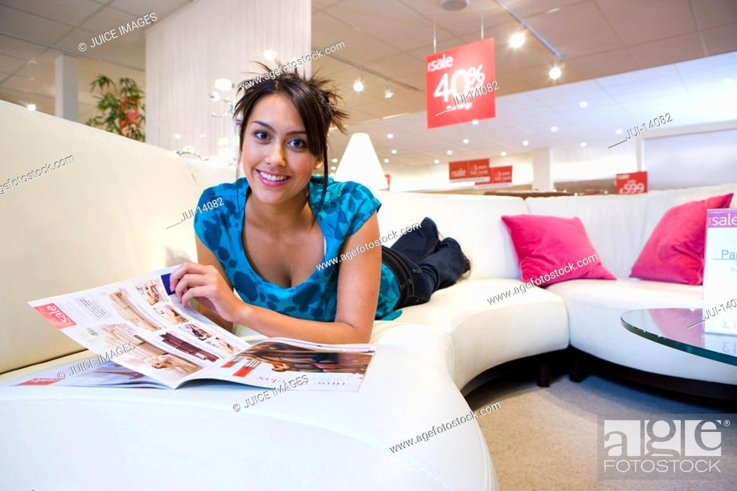 Stock Photo: Young woman with brochure on sofa in shop, smiling, portrait.