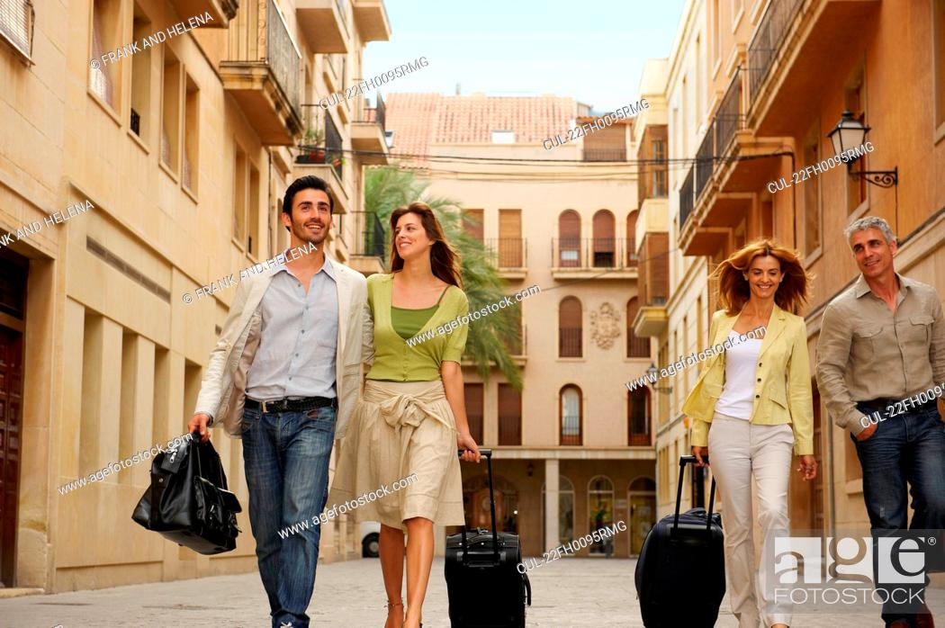 Stock Photo: Two couples with cases walking.