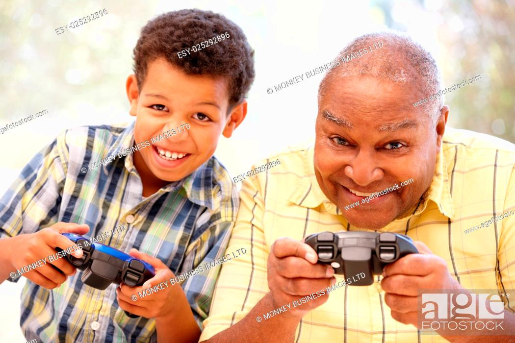 Stock Photo: Grandfather and grandson playing computer games.
