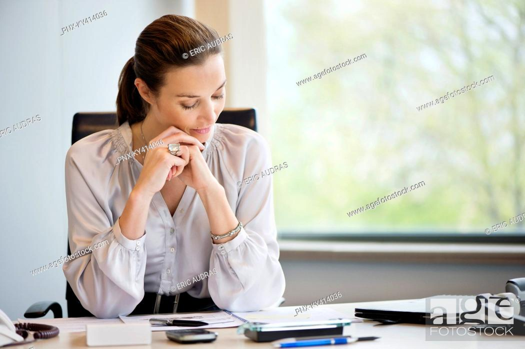 Stock Photo: Businesswoman reading documents in an office.
