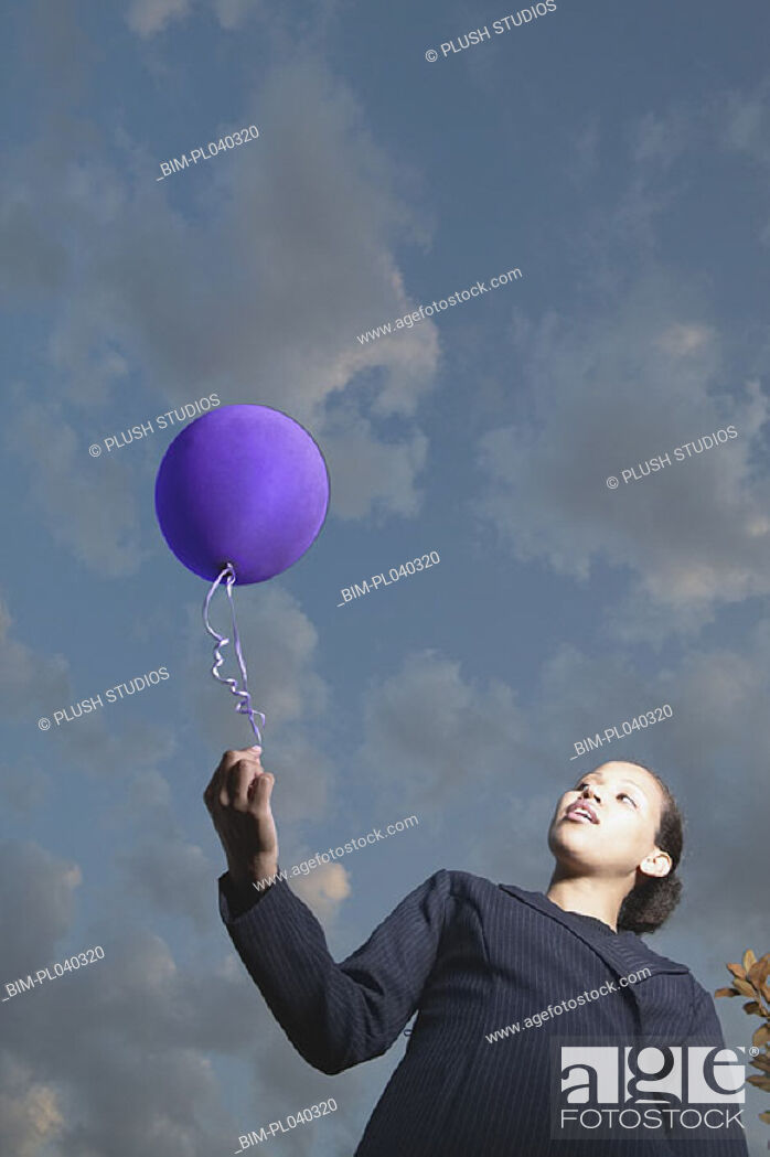 Stock Photo: Low angle view of businesswoman with balloon.