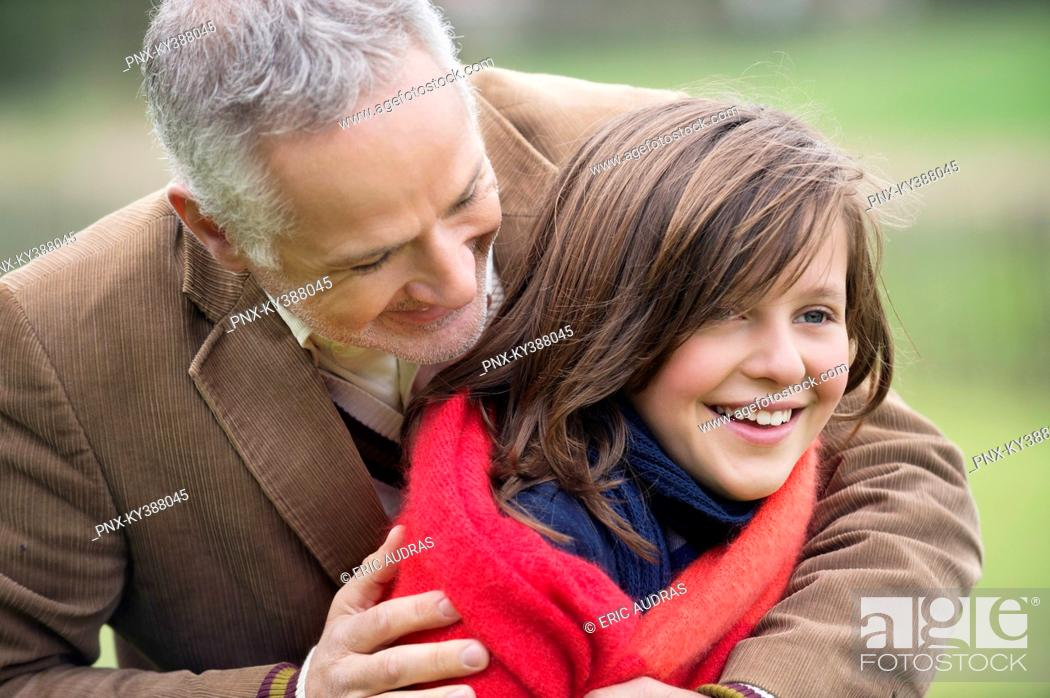 Stock Photo: Man hugging his daughter in a park.