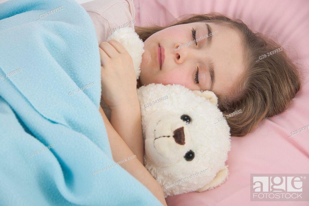 Stock Photo: Little girl asleep in bed cuddling her teddy bear.