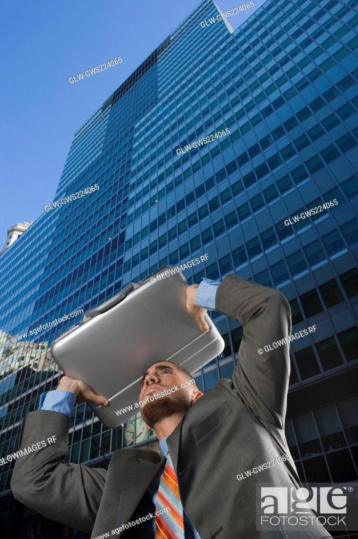 Stock Photo: Low angle view of a businessman using his briefcase as a shade.