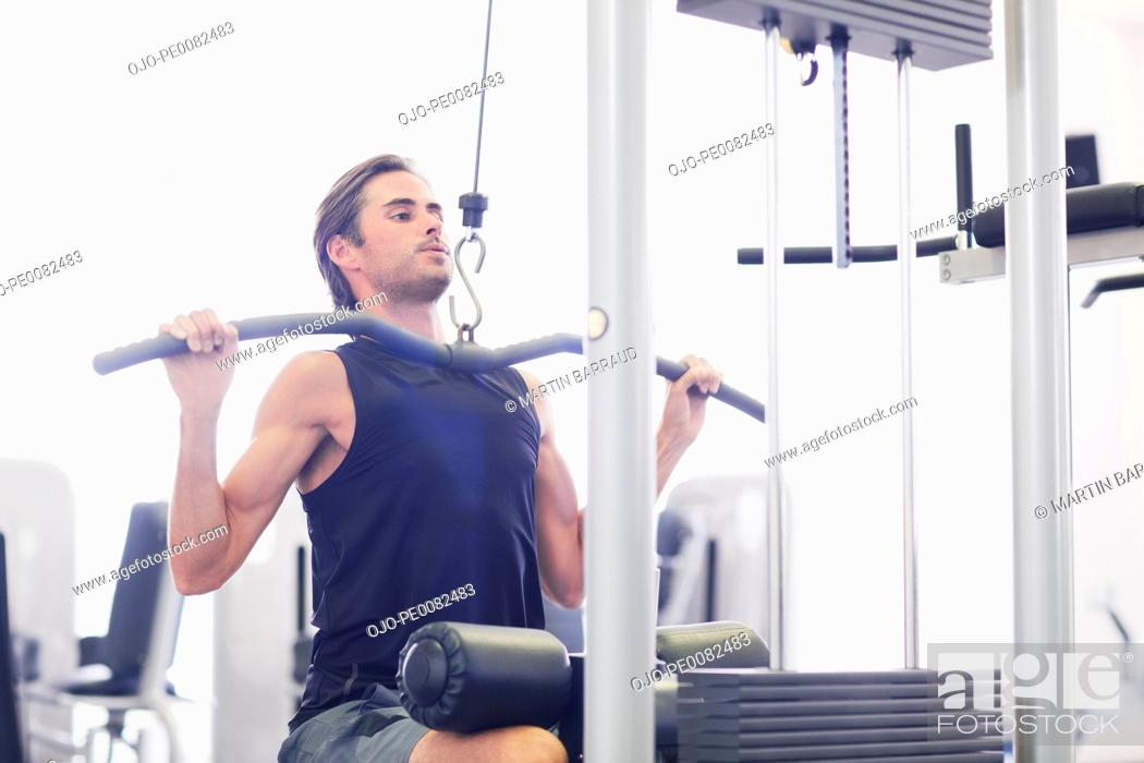 Stock Photo: Man using exercise machine in gymnasium.