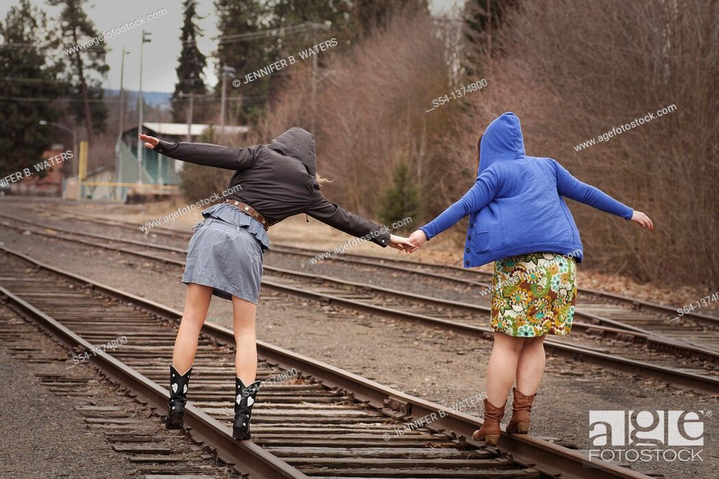 Stock Photo: Two young women walking together on railroad tracks.