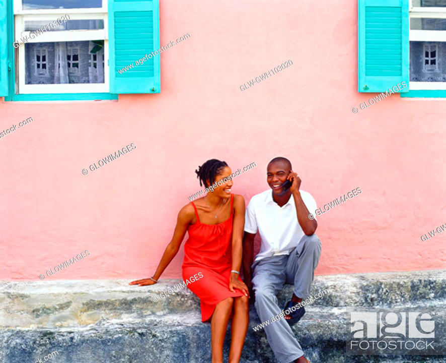 Stock Photo: Young couple sitting in front of a house and talking on a mobile phone, Bermuda.