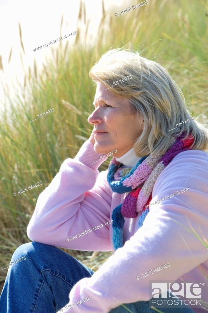 Stock Photo: Mature woman sitting on beach.