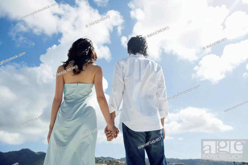 Stock Photo: Rear view of a young couple holding hands.
