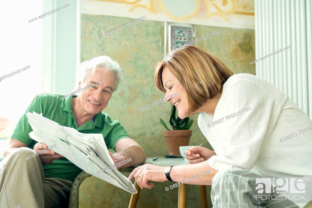 Imagen: Couple reading newspaper together, smiling.