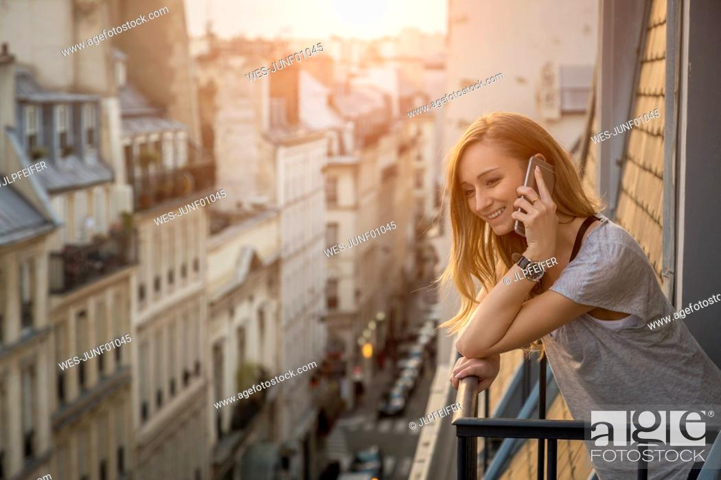 Stock Photo: France, Paris, portrait of smiling woman on the phone standing on balcony in the evening.