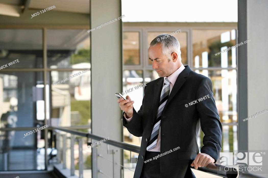 Stock Photo: Businessman leaning on railing using mobile phone.