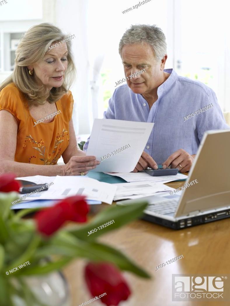 Stock Photo: Senior couple looking at bills sitting at dining table.