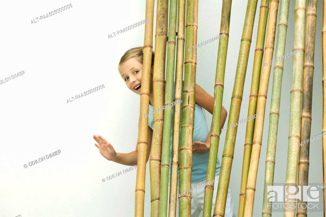 Stock Photo: Girl standing behind bamboo, smiling and waving at camera.