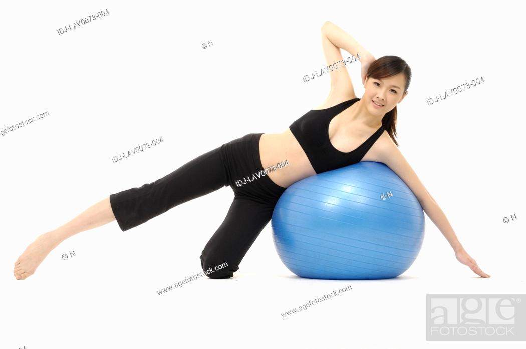 Stock Photo: Woman stretching using an exercise ball.