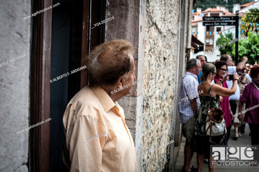 Stock Photo: A man watches the procession pass at the door of his house. Llanes. Asturias Spain.