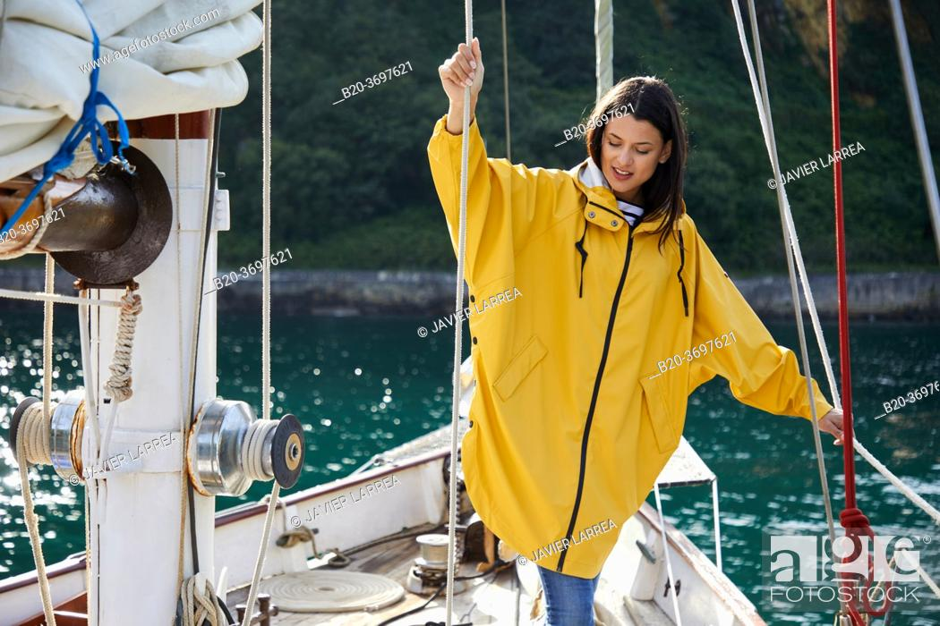 Imagen: Young woman with raincoat, Sailing boat, Pasaia port, Gipuzkoa, Basque Country, Spain, Europe.