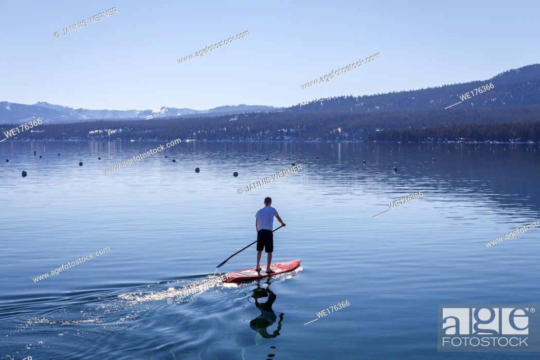 Stock Photo: Young man seen from behind as he standup paddles at Lake Tahoe.