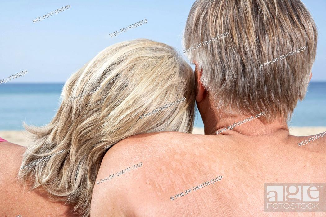 Stock Photo: Spain, Mallorca, Senior couple sitting at beach.