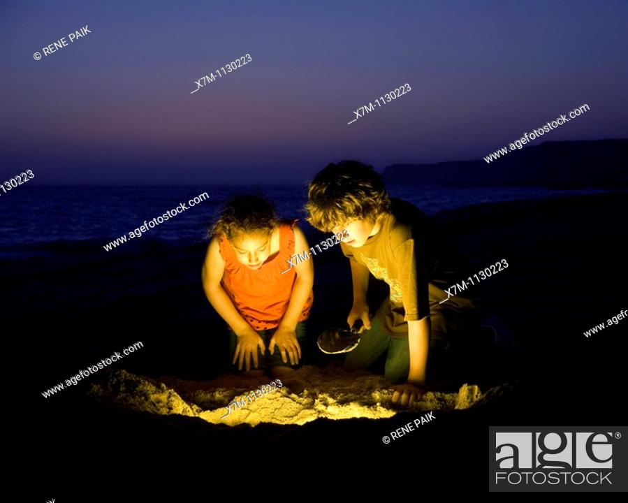 Stock Photo: Kids find treasure after digging on a sandy beach.