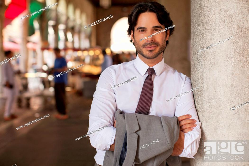 Stock Photo: Portrait of smiling businessman leaning on pillar with arms crossed.