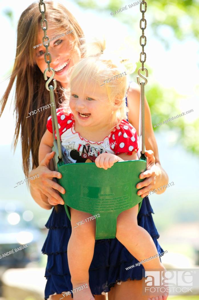 Stock Photo: Young mother with two years old female child on a swing in a park.