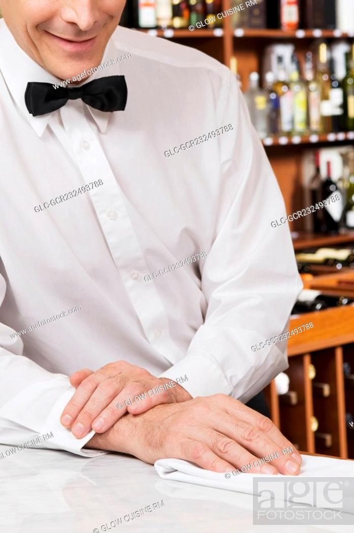 Imagen: Waiter leaning against a bar counter.