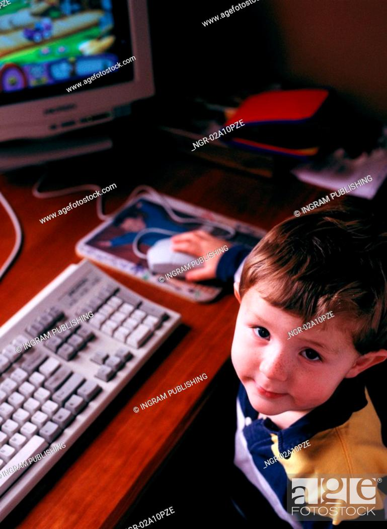 Stock Photo: little boy working on a computer.