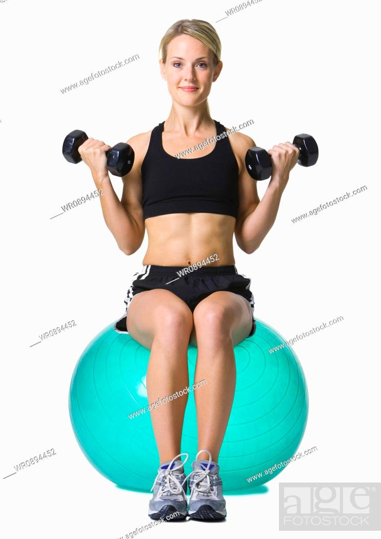Portrait Of A Young Woman Sitting On A Fitness Ball Holding