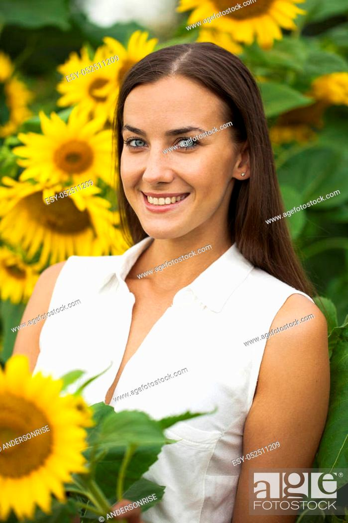 Stock Photo: Happy young brunette woman with sunflowers, summer outdoors.