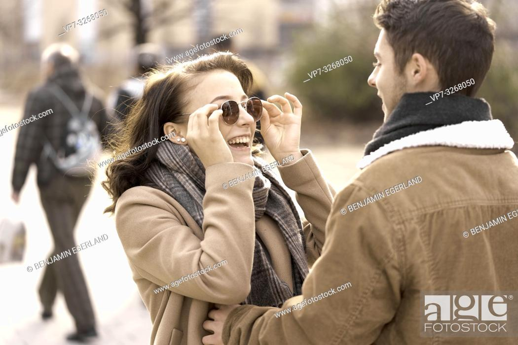 Stock Photo: enthusiastic teenage woman touching sunglasses while looking at boyfriend, in Cottbus, Brandenburg, Germany.