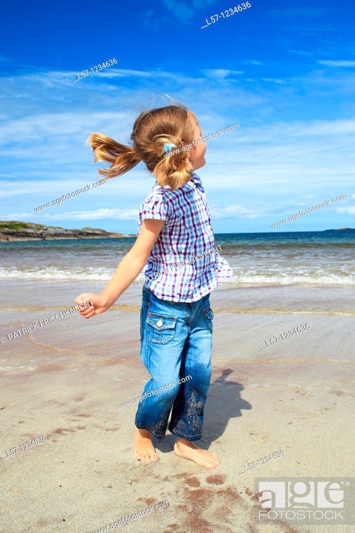 Stock Photo: girl playing on sandy beach, Sutherland, Scotland.