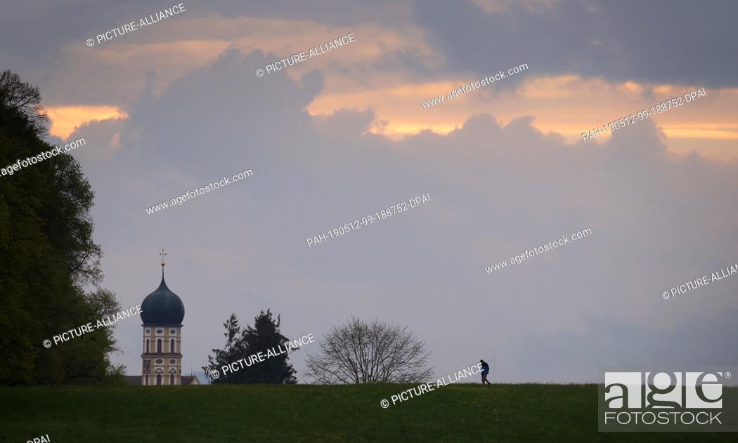 Imagen: 12 May 2019, Bavaria, Marktoberdorf: A walker walks under thinning clouds in front of the tower of the parish church Sankt Martin.