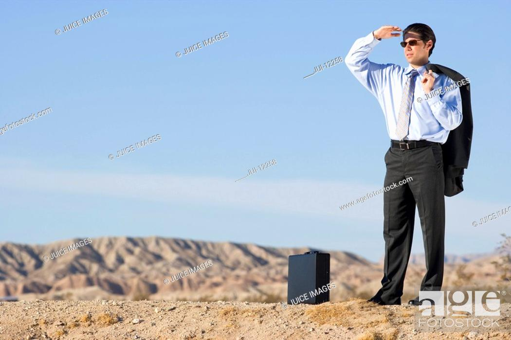 Stock Photo: Businessman in sunglasses with briefcase in desert, looking into distance.