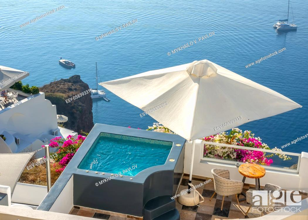 Imagen: Santorini. Terraces on the high shore of Thera Island. Swimming pool and loungers for relaxing in sunny weather. Yachts by the shore.